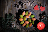Walnut cookies with Dulce De Leche or condensed milk. Yummy sweets on dark rustic wooden boards. Natural sunlight, long shadows. Fir twigs decorated with pine cones, red candle and wooden heart