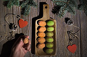 Walnut shaped cookies with Dulce De Leche or sweetened condensed milk. Tasty creative dessert on dark wooden table with natural decorations - fir twigs, wooden hearts and frosted cones. Cookie in hand