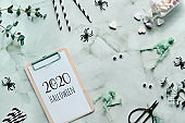 2020 Halloween text on clipboard pad on mint green stone background. Flat lay with bottle of sugar heart candy, spiders, skeletons, paper straws and eucalyptus.