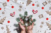 Christmas flat lay with female hands holding decorated fir twigs. Zero waste eco friendly decor - recycled paper confetti, candy cane hearts, Xmas tree silhouettes and snowflakes.
