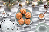 Creative flat lay with yummy eclairs or brewing cakes. White ceramic tea pot, cup of tee, sugar, heart candy. Christmas tree garland, fir twigs with lights on light stripy textile