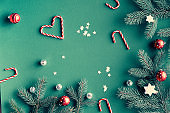 Christmas flat lay with fir twigs decorated with red baubles, candy canes and paper star confetti