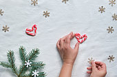 Christmas flat lay with female hands holding heart from candy canes and craft paper snowflake. Eco friendly decorations - natural fir Xmas tree twigs, paper confetti on white textile background.