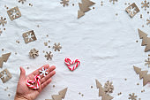Christmas flat lay on white textile. Hand holds snowflake and red white stripy candy cane heart. Eco friendly decor from craft paper - Xmas tree silhouettes, snowflakes in brown, red and white.