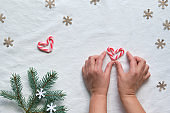 Christmas flat lay with female hands holding heart from candy canes. Zero waste eco friendly decor from natural fir Xmas tree twigs, recycled paper confetti, sweets