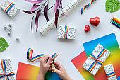 Christmas gifts with rainbow ribbon in LGBTQ flag colors. Flat lay with Xmas decor on white