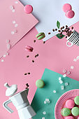 Levitation and balance composition. Flying macaroons, ceramic coffee maker and espresso coffee cup. Geometric layered paper background in pastel colors, pink, cream and light green