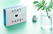 "Lightbox with text ""Stay safe"", glass bottle with palm leaf and wooden heart. Wishing well to friends and family during quarantine and social distancing due to Covid-19 pneumonia in many countries"