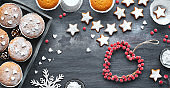 Christmas background with star cookies, tasty lemon muffins, winter decor with fir and berries