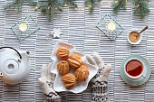 Creative Xmas table setup for tea with cakes. Creative flat lay with yummy eclairs or brewing cakes. Christmas tree shape plate with cakes. Fir twigs with light garland on stripy textile tablecloth