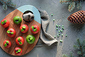 Marzipan sponge apples. Christmas dessert on wooden board. Winter decor, fir twigs and pine cone