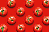 Fresh tomatoes isolated on red background.