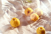 Close-up on ripe sweet Japanese quince fruits on dark table with linen tower. Autumn decorations, natural Fall colors.