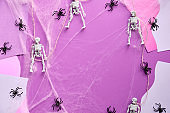 Split Halloween paper background with red paper buts, skeletons, spider web and spiders on pink, purple and white abstract background. Creative flat layout..
