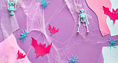 Split Halloween paper background with red paper buts, skeletons and spiders on pink, purple and white abstract background. Creative top view.