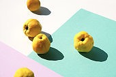 Close-up on Japanese quince fruits. Geometric layered paper. Long shadow design. Pastel colors, yellow, pink and mint green color palette.
