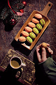 Walnut shaped cookies with Dulce De Leche or sweetened condensed milk. Creative flat lay on dark table decorated with fir twigs, cones, red ribbons and cup of coffee on old book. Hand with cookie