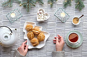 Creative table setup for Xmas tea. Creative flat lay with eclairs or brewing cakes. Christmas tree shape plate with cakes, female hands. Stripy textile background. Fir twigs with light garland