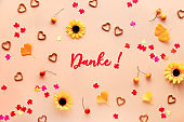 Danke means Thank you in German language. Fall decorations - yellow flowers, orange gingko leaves, maple leaf paper confetti, cord and heart shape pretzels. Autumn flat lay on orange background.