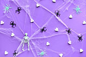 Creative Halloween background with white sugar hearts, spider web and black spiders on vibrant purple neon paper. Flat lay, trendy background.