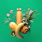 Assortment of tropical fruits around smoothie bottle on green background. Pineapple, kiwano, kiwi , lichee and banana - exotic fruits, square composition, levitation and vitamin balance.