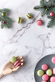 Pink and mint green macaroons in wooden hand and on grey plate. Tasty creative dessert in green and red on marble table with fir twigs