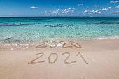 New year 2021 written on the beach.