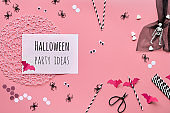 Hexagon confetti, paper drink straws, bats, sugar hearts and spiders. Pink Halloween background, top view, text Halloween party ideas.
