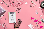 Flat lay, hand in glove, scissors and Halloween decor. Hexagon confetti, drink straws, bats, sugar hearts, black spiders. Trick or treat text on pink paper background.