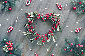 Decorative heart shaped mistletoe wreath. Wooden Christmas background decorated with natural fir twigs, red white Xmas stripy candy canes and red berries.