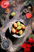 Walnut cookies with Dulce De Leche or condensed milk in vintage tin bowl. Tasty sweets on dark textured background with decorations. Old clock, fir twigs, poinsettia, red candle and wooden heart