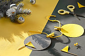 Illuminating Yellow and Ultimate Gray, colors of the year 2021. Fir twigs and DIY Christmas decorations on split yellow grey paper on table