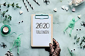 2020 Halloween text on clipboard pad in hand. Top view with scissors, bottle of sugar heart candy, spiders, skeletons, paper straws and eucalyptus.