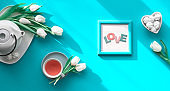 Spring geometric flat lay. Female hand hold frame with text You are special. Tea cup, pot, sweets and white tulips on turquoise. Mothers day, international women day 8 March or your Mom birthday.