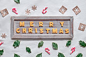 ext Merry Christmas made with cookies on rustic wooden board. Geometric flat lay on white textile background. Zero waste decor from craft paper , candy canes and natural holly leaves.