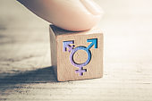 Transgender, LGBT or Intersex Icon On A Wodden Block On A Table Arranged By A Finger