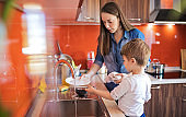 Mother and cute son doing the dishes