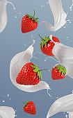 Fresh strawberries falling into milk.