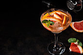 Grapefruit cocktail in a martini glass with mint and ice cubes.