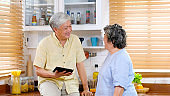 Senior asian couple talking while standing by window in kitchen background, Happy edlerly asia, Old people retirement family holding digital tablet while talking at home