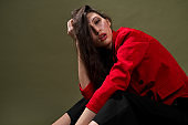 A sensual young woman in a red jacket, culottes and shoes with wet long black hair poses against a green background in the studio.