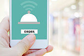 Food online, delivery, Man hand ordering food by mobile phone, Smartphone app on screen device over blur restaurant background with copy space, business and technology, lifestyle, stay home