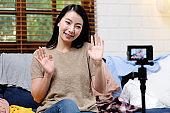 Asian blogger, Asia woman fashion blogger, influencer greeting while recording new content for vlog and fashion online shopping with camera at home studio, Freelance occupation, small business owner