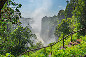 Victoria Falls on Zambezi River, border of Zambia and Zimbabwe with blue sky and a walking way