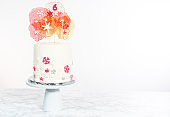 Tall round cake with Italian buttercream frosting decorated