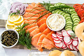 Bagel brunch board with smoked salmon and fresh vegetables.