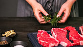 Raw New York strip steaks on a wood cutting board.