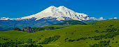 Elbrus and Green Meadow Hills at a Summer Day. Panoramo