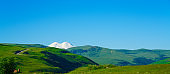 Elbrus and Green Meadow Hills at a Summer Day. Panorama