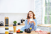 Beautiful and cute young girl at home in the kitchen with a Cup in her hands in everyday clothes